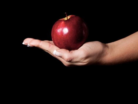 Woman holding red apple on black background