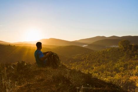mężczyzna-siedzi-na-wzgorzu-w-krajobraz-zachodu-słońca_23-2147665061